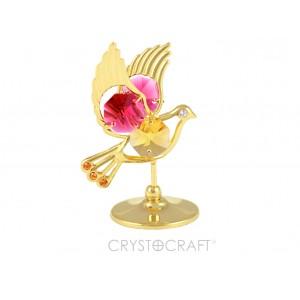 Balodis uz pamatnes, zelta pārklājums, ar sarkanām un dzeltenām kristāliem. Izmērs 4.5 x 6 cm.