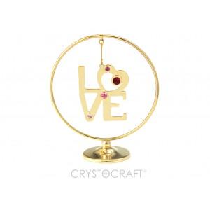 Uzraksts LOVE iekārts ķēdītē aplī, ar SWAROVSKI kristāliem, uz pamatnes, zelta pārklājums. Izmērs 7,1 x 8 cm.