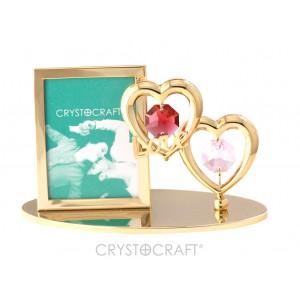 Fotorāmītis ar divām sirdīm, uz pamatnes, ar SWAROVSKI kristāliem, zelta pārklājums. Izmērs 10 x 4,5 x 7,5 cm. Fotogrāfijas izmērs: 3,7*5 cm.