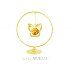 Tauriņš iekārts ķēdītē aplī, ar SWAROVSKI kristālu, uz pamatnes, zelta pārklājums. Izmērs 5 x 7 cm.