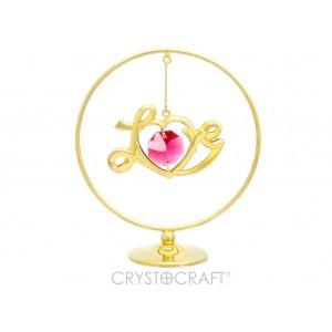 """Uzraksts """"Love"""" iekārts ķēdītē aplī, ar SWAROVSKI kristāliem, uz pamatnes, zelta pārklājums. Izmērs 5 x 7 cm."""